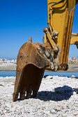 Diggers on the seashore building a breakwater — Stock Photo