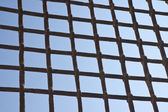 Metal grate against a blue sky - freedom concept — Stock Photo