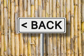 """The word """"Back"""" written on a road sign against a fence wattle — Stock Photo"""