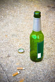 Bottle of beer resting on the ground — Stock Photo