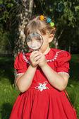Girl looking through magnifiying glass at grass outdoors — Stock Photo