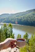 Cup of tea by a river in the afternoon — Stock Photo