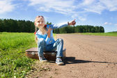 Girl with suitcase standing about road — Foto Stock