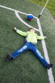 Little boy soccer ball lying on  grass — Stock Photo