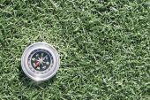 Classic compass on grass field — Stock Photo