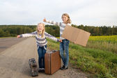 Two girls with suitcase standing about road — Stock Photo