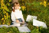 Beautiful  girl reading letter while sitting on the tree — Stock Photo