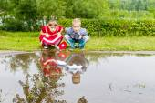 Little sister and brother playing with paper boats — Stock Photo