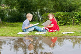 Gelukkig jong meisje en jongen schrijven. Glimlachend in zomertuin. — Stockfoto