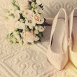 Bouquet of white roses, rings and satin wedding shoes on chair — Stock Photo #57711347