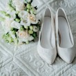 Bouquet of white roses, rings and satin wedding shoes on chair — Stock Photo #57711989