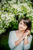 Elma ağacının yanında duran güzel genç esmer kadın — Stok fotoğraf
