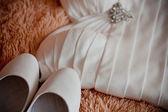 букет из белых роз, кольца и атласная свадебная обувь на стуле — Стоковое фото