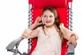 Girl talking on the phone sitting in an armchair — Zdjęcie stockowe