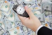 Wristwatch on dollars background — Stock Photo