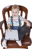 Boy in the chair writes — Stock Photo