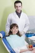Portrait of happy young dentist and patient in clinic — Stock Photo