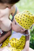 Mother breastfeeding a baby in nature — Stock Photo