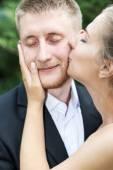Bride kisses groom on the cheek — Stock Photo