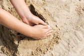 Child hand on a sand — Stock Photo
