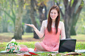 Women sitting on wooden mat and holds a sign on parkland. — Stock Photo