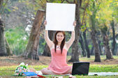 Women sitting on wooden mat and holds a sign at parkland. — Stock Photo