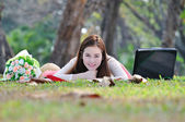 Woman sitting on wooden mat and smiling. — Stock Photo