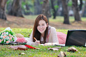 Woman sitting on wooden mat and writing notepad at parkland. — Foto de Stock