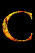 C fire letter cracked on black background — Stock Photo
