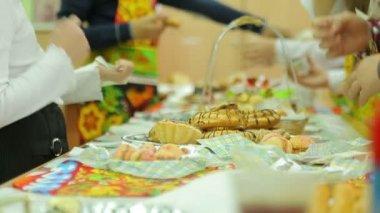 Charity fair, girl chooses cake — Stock Video