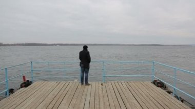 Sad pensive man standing on the pier — Stock Video