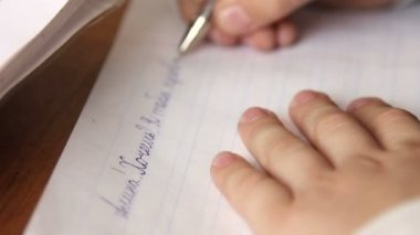 Pupil at the school wrote on a piece of note paper, close-up — Vídeo de stock