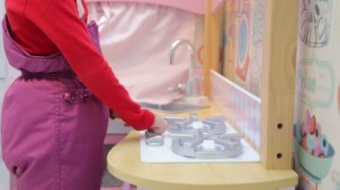 Girl playing with a toy kitchen turns on a gas stove and washes his hands under the tap — Stock Video