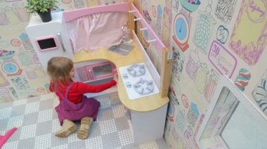 Girl playing with a toy kitchen, top view — Stock Video