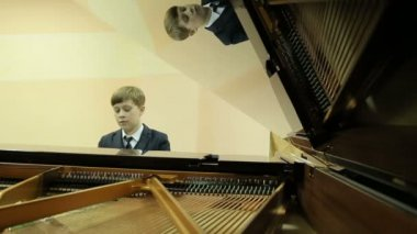 Boy playing the grand piano with the lid open — Stock Video