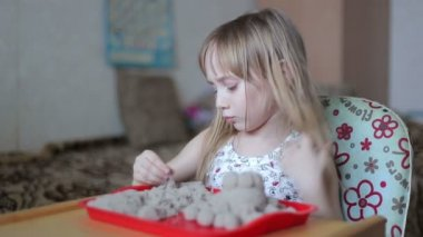 Little girl sculpts figures out of the sand — Stock Video