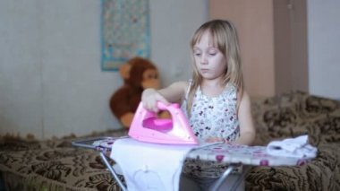 Little girl is ironing clothes — Vídeo stock
