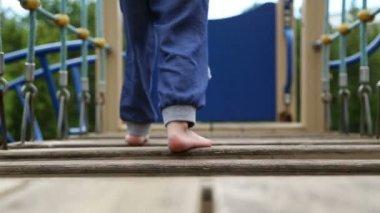 Мальчик ходит босиком на площадке — Стоковое видео