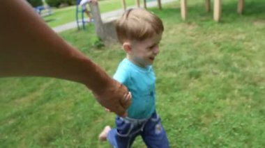Boy runs, holding his father's hand — Stock Video