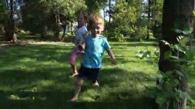 Dívka a chlapec běží naboso na trávě — Stock video