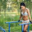 Beautiful fitness woman doing exercise on parallel bars sunny outdoor. Sporty girl doing push ups on bars outdoor — Stock Photo #52938971