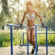 Beautiful fitness woman doing exercise on parallel bars sunny outdoor. Sporty girl doing push ups on bars outdoor — Stock Photo #52939009