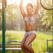 Sexy young fitness girl pulls up on street sport gym. Brunette fitness woman in sport wear with perfect fitness body on street workout performing abdominal exercises on the horizontal bar — Stock Photo #52939045