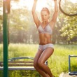 Sexy young fitness girl pulls up on street sport gym. Brunette fitness woman in sport wear with perfect fitness body on street workout performing abdominal exercises on the horizontal bar — Stock Photo #52939055