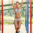Sexy young fitness girl pulls up on street sport gym. Brunette fitness woman in sport wear with perfect fitness body on street workout performing abdominal exercises on the horizontal bar — Stock Photo #52939061