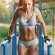 Beautiful fitness woman doing exercise on parallel bars sunny outdoor. Sporty girl doing push ups on bars outdoor — Stock Photo #52939069