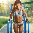 Beautiful fitness woman doing exercise on parallel bars sunny outdoor. Sporty girl doing push ups on bars outdoor — Stock Photo #52939081