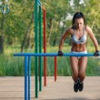 Beautiful fitness woman doing exercise on parallel bars sunny outdoor. Sporty girl doing push ups on bars outdoor — Stock Photo #52939103