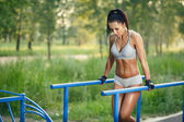 Beautiful fitness woman doing exercise on parallel bars sunny outdoor. Sporty girl doing push ups on bars outdoor — Stock Photo