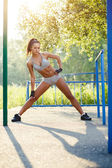 Pretty woman doing sport stretching exercises and relax in the summer outdoor. — Stock Photo